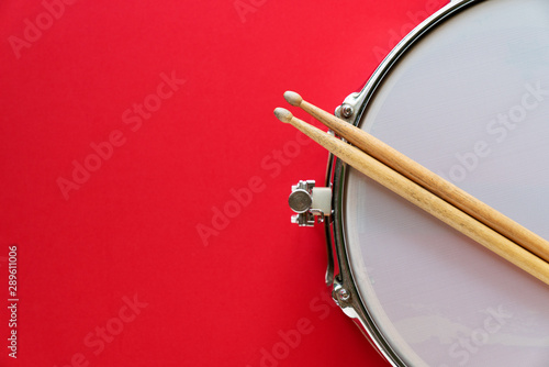 Canvas Print Drum and drum stick on red table background, top view, music concept