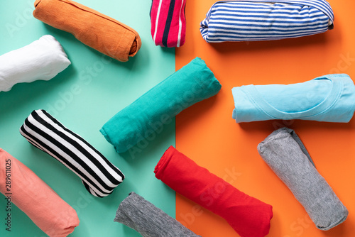 Obraz na plátně  close up of rolled colorful clothes on color background