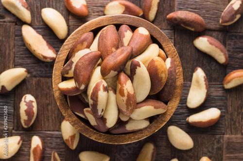 Fotografia brazilian nuts peeled in wooden bowl, top view.