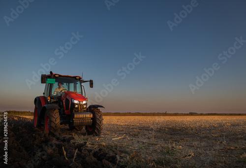 Tractor plowing fields in sunset Wallpaper Mural