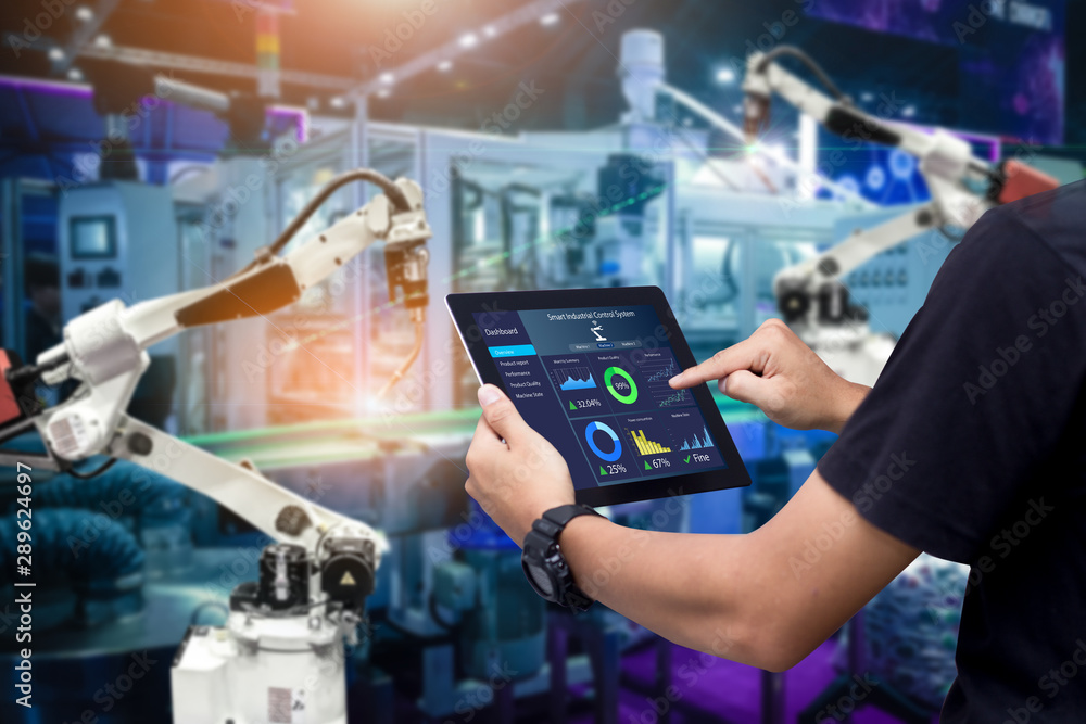 Fototapety, obrazy: Smart industry control concept.Hands holding tablet on blurred automation machine as background
