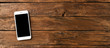 Overhead shot of white smart phone with copyspace on retro wooden background. Banner