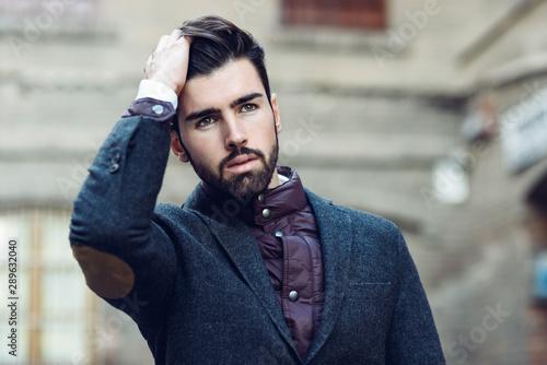 Pinturas sobre lienzo  Young bearded man wearing british elegant suit touching his hair