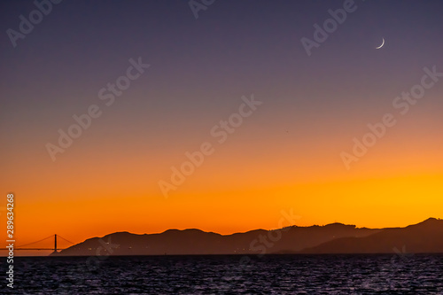New moon sickle glistens over the Golden Gate Bridge at sunset. Fototapet