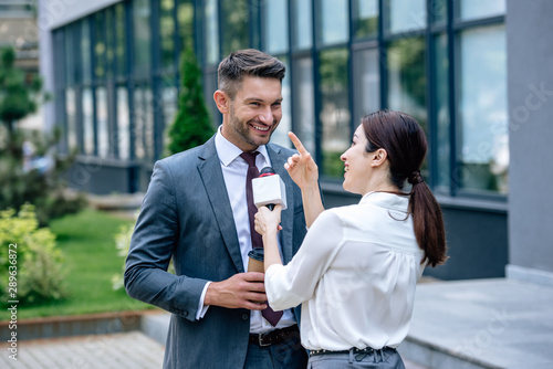 Obraz journalist holding microphone and talking with businessman in formal wear - fototapety do salonu
