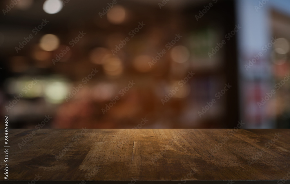 Fototapeta Empty dark wooden table in front of abstract blurred bokeh background of restaurant . can be used for display or montage your products.Mock up for space.