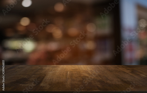 Fototapeta Empty dark wooden table in front of abstract blurred bokeh background of restaurant . can be used for display or montage your products.Mock up for space. obraz