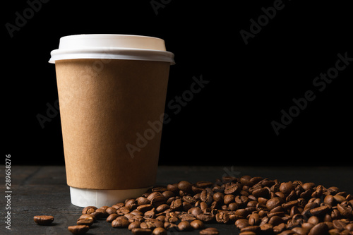 Door stickers Cafe Paper cup of coffee and coffee beans on dark wooden table. Good quality coffee