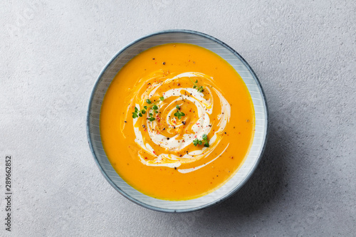 Poster Individuel Pumpkin and carrot soup with cream on grey stone background. Top view.