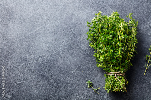 Fotografía  Fresh thyme bunch on slate background. Top view. Copy space.