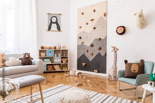 Stylish scandinavian interior design of childroom with gray sofa, modern climbing wall for kids, design furnitures, soft toys, teddy bear and cute children's accessories. Mock up poster. Template.