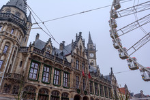 Ferris Wheel In The Ghent City Center Near Gothic Old Post Office Building In Foggy Winter Morning Against Cold Grey Sky.