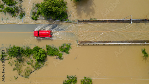 Fotografía Aerial top view of Flooded the village and Country road with a red car, View fro