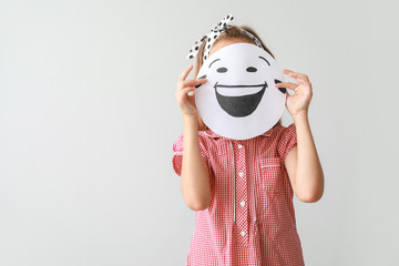 Little girl hiding face behind drawn emoticon on light background