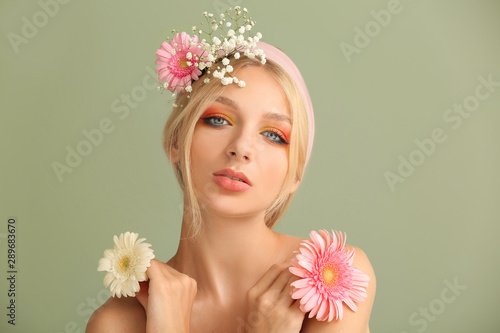 Beautiful young woman with flowers on color background - 289683670