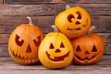 Funny Halloween Pumpkins On Wooden Background. Group Of Pumpkins Carved For Halloween Party. Traditional Holiday Of Fall.