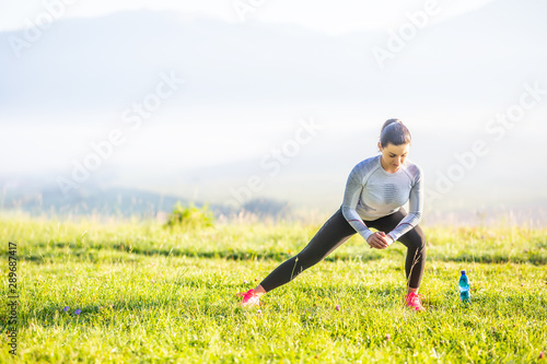 Cuadros en Lienzo Young fitness woman runner stretching legs before run in autumn nature