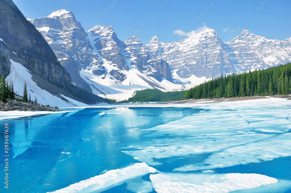 Fototapeta Moraine lake under the ice at morning spring time. Banff National park. Canada.