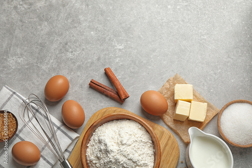 Flat lay composition with fresh ingredients for delicious homemade cake on light grey marble table. Space for text