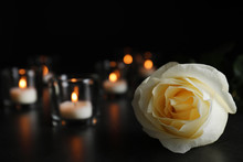 White Rose And Blurred Burning Candles On Table In Darkness, Closeup With Space For Text. Funeral Symbol