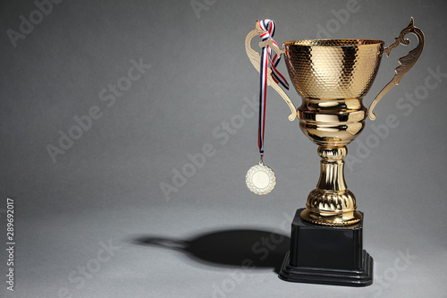 Fotografie, Obraz  Golden trophy cup and medal on grey background. Space for text