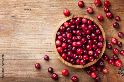 Obraz Ripe cranberry in wooden bowl on rustic table top view. - fototapety do salonu