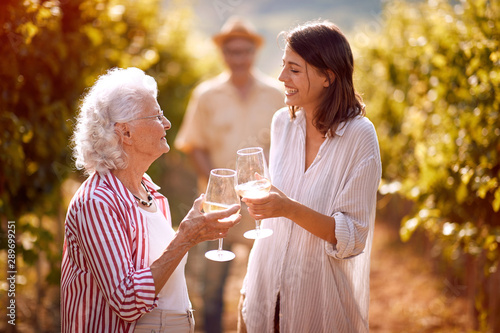 Fotografía family in vineyard tasting wine.