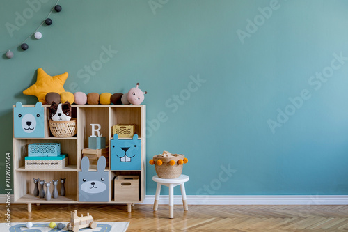 Stylish scandinavian newborn baby room with wooden cabinet, toys, children's chair, natural basket Modern interior with eucalyptus background walls, wooden parquet and cottona balls. Home decor.