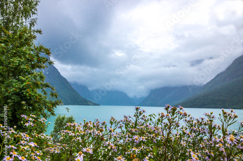 Cadres-photo bureau Bleu jean rain clouds over Lovatnet lake in Norway