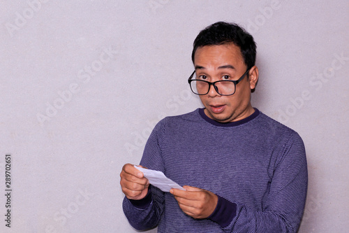 Pinturas sobre lienzo  an asian man raise the eyebrows and make it down his glasses while holding white mail paper