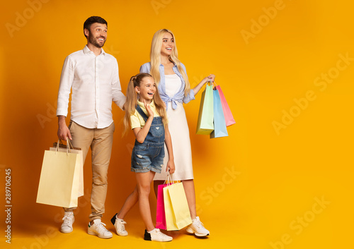 Parents And Daughter Walking Holding Shopping Bags, Yellow Background Canvas-taulu