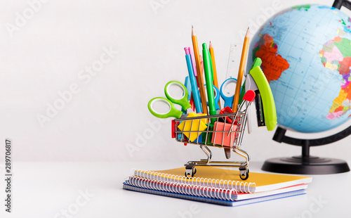 Obraz Shopping cart with stationary and geographical globe on white - fototapety do salonu