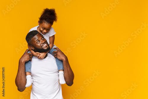 Cute african girl sitting on daddy's shoulders Fotobehang