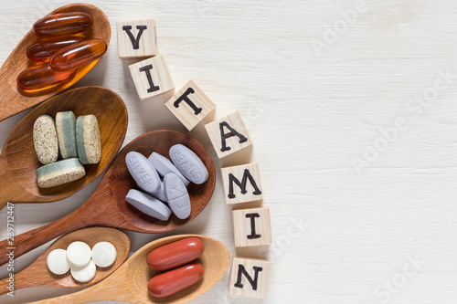 Carta da parati Variety of vitamin pills in wooden spoon on white background, supplemental and h
