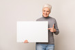 canvas print picture - Senior woman holding blank advertising board and pointing on it