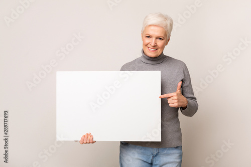 Cuadros en Lienzo  Senior woman holding blank advertising board and pointing on it