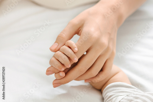 Fotografie, Obraz  Tiny fingers of newborn baby holding mother's hand, closeup