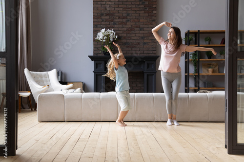 Obraz Overjoyed young mother dancing with little cute adorable smiling daughter. - fototapety do salonu