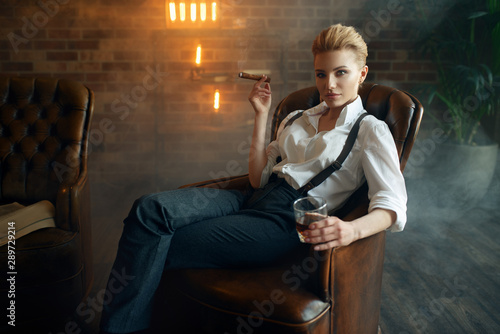 Tablou Canvas Woman sitting in chair with whiskey and cigar