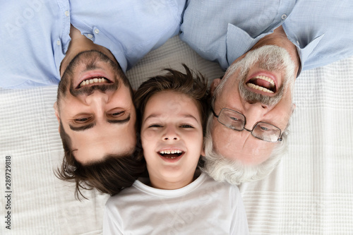 Happy three generation family lying in row, portrait, closeup view