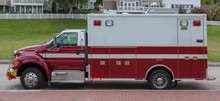 Front Side View Of Red And White Ambulance Parked On Residential Street With Lights Flashing.