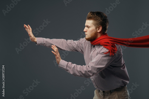 Obraz Strong wind blowing on man in red scarf - fototapety do salonu