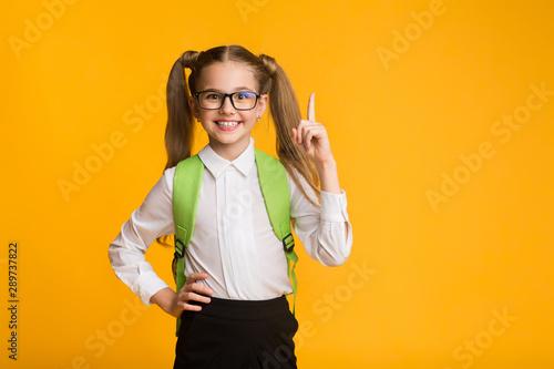 Obraz Little Schoolgirl Pointing Finger Up Over Yellow Background, Studio Shot - fototapety do salonu