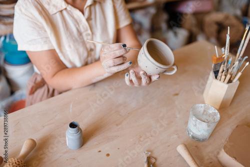 Fotografía  Female master paints a pot, pottery workshop