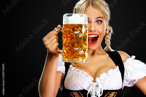 Cuadros en Lienzo Smiling young sexy oktoberfest girl waitress, wearing a traditional Bavarian or german dirndl, serving big beer mug with drink isolated on black background