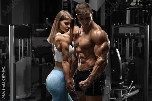 Sporty sexy couple showing muscle and workout in gym Fototapet