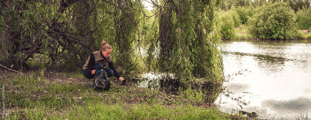 Fototapeta Recycle waste litter rubbish garbage trash junk clean training. Nature cleaning, volunteer ecology green concept. Young woman pick up spring forest at sunset . Environment plastic pollution banner