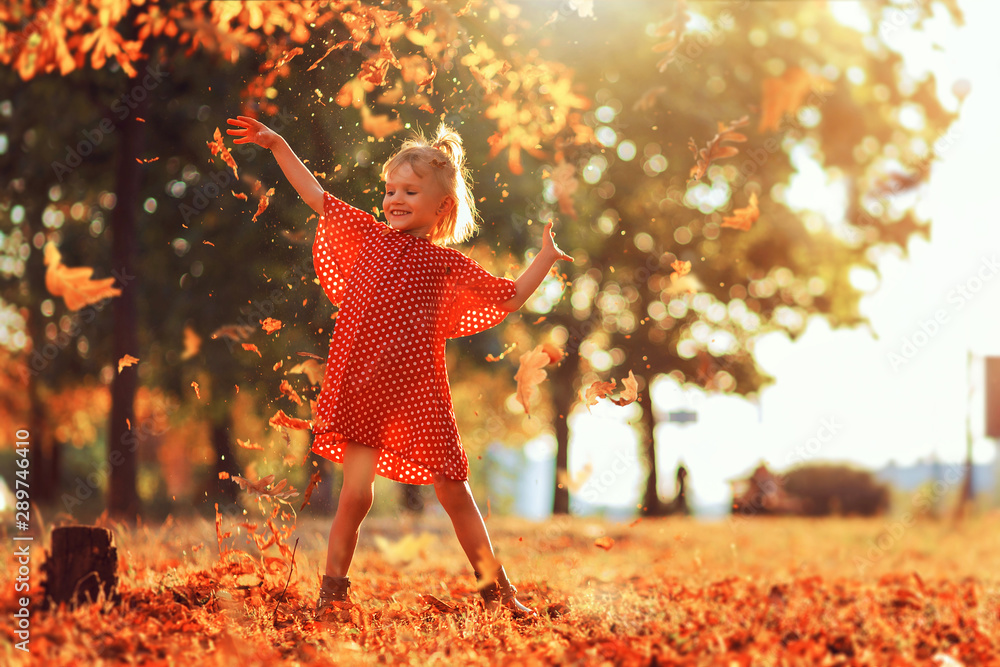 Fototapeta Journey in nature. Adorable happy girl throwing the fallen leaves up, playing in the autumn park. Little blonde hair and blue eyes girl smiling expression. Girl in polka dot red dress and boots