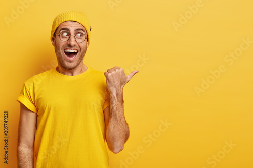Follow this way. Happy young man with overjoyed face expression, points thumb away on right side, discusses interesting advertisement, expresses good emotions, wears vivid clothes, yellow background