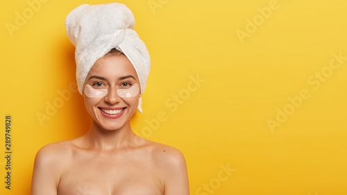 Fotografía  Studio shot of beautiful young woman with healthy delicate fresh skin under eyes, wears towel on head, applies patches for reducing fine lines, stands naked against yellow background